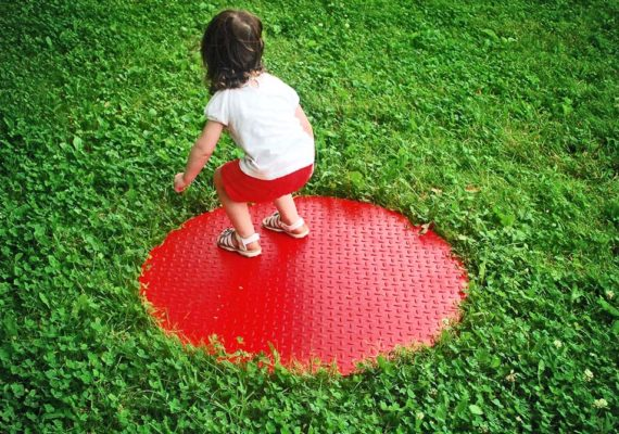 toddler stands in a red circle