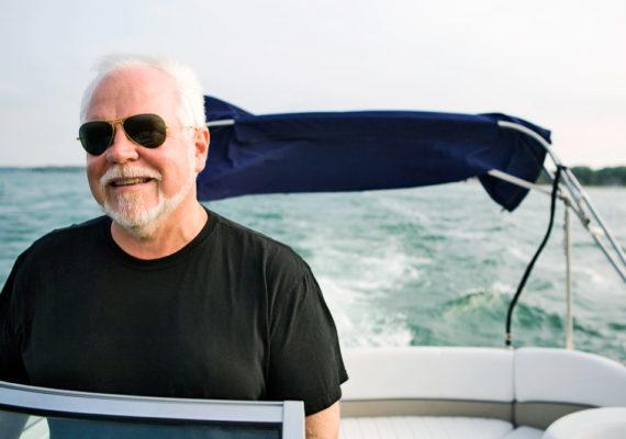 older man drives boat