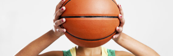 woman holds a basketball in front of her face
