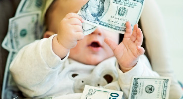 baby plays with $100 bills