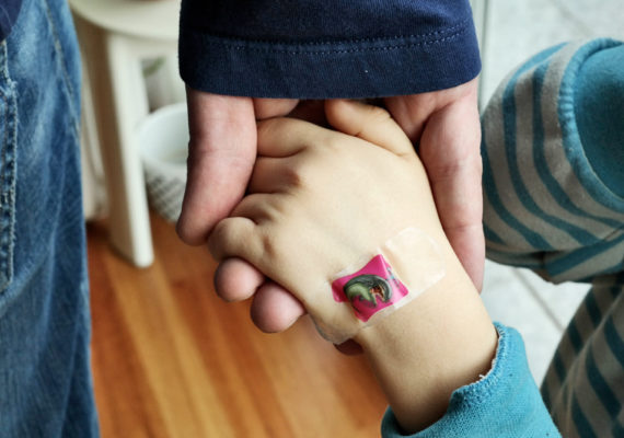 dad holds kid's hand with bandaid