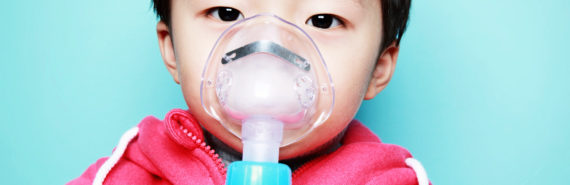 child in pink hoodie with nebulizer