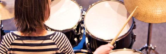 teen girl plays drums