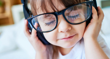 child with glasses and headphones