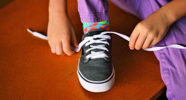 child tying shoelaces