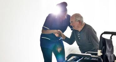 nurse helps older man up