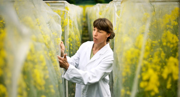 woman in lab coat with plants