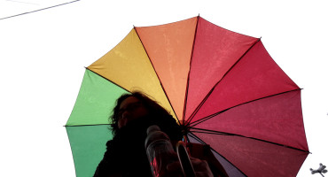silo person under rainbow umbrella