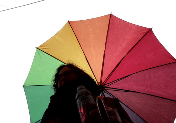 silo person under rainbow umbrella