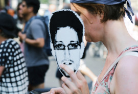 woman holds Snowden sign & phone