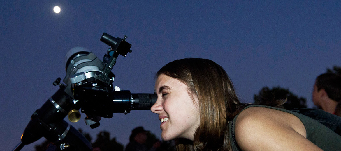 young woman uses telescope