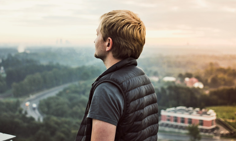 young guy looks out from hill