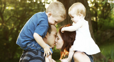 couple with 2 kids kisses