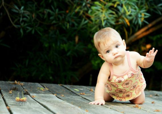baby crawls on a wood deck