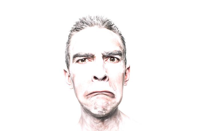 man in white paint looks horrified