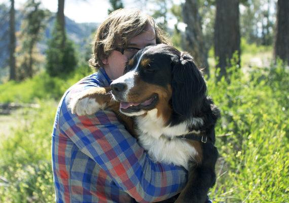 man hugs a dog