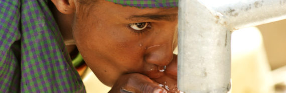 child drinks from water pipe