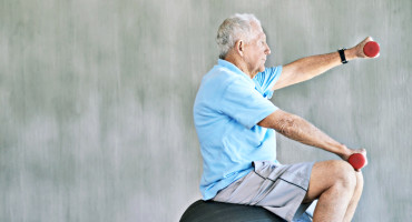 elderly man with weights & exercise ball