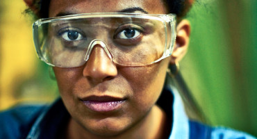 woman wears safety glasses at work
