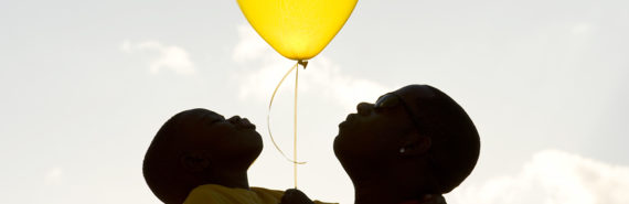silhouette of father and son holding a balloon