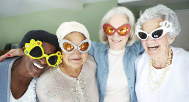 four women wearing funny glasses