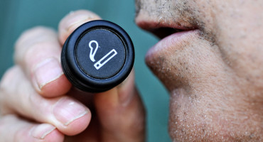 man holds lighter to mouth