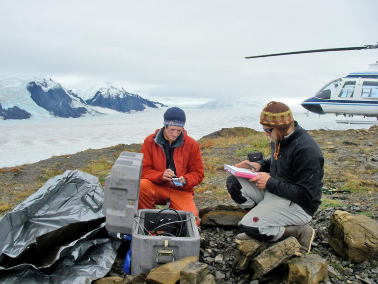 Researchers work with seismic equipment to track meltwater running through Alaska's Yahtse Glacier.