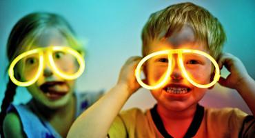 two kids wear neon glasses