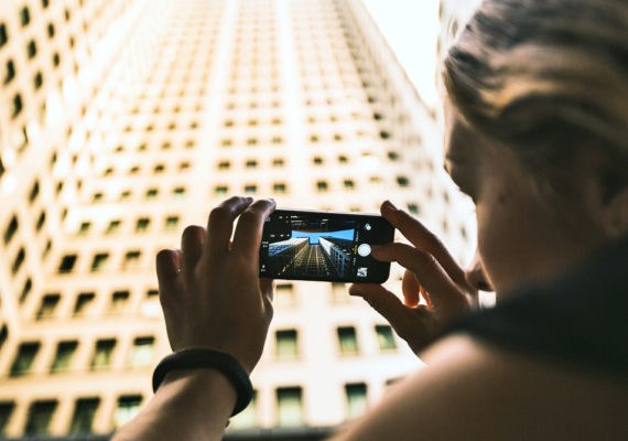 woman takes photo of building