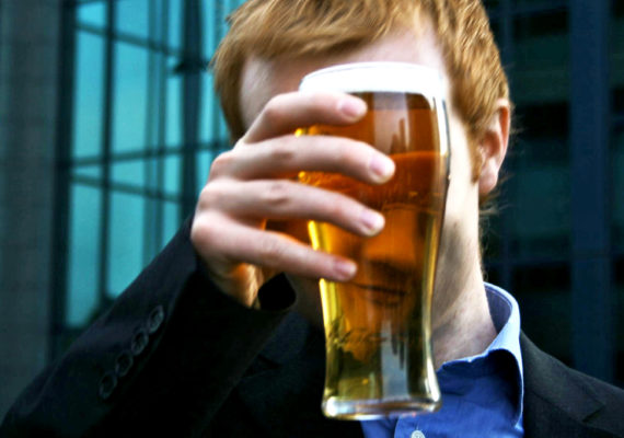 man holds pint of beer