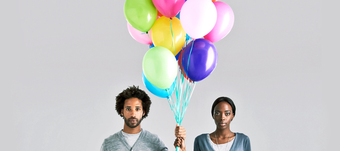 Black man and woman hold balloons