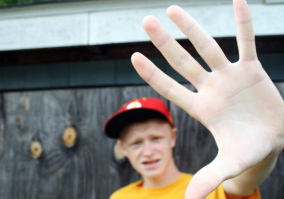 teenage boy holds up his hand