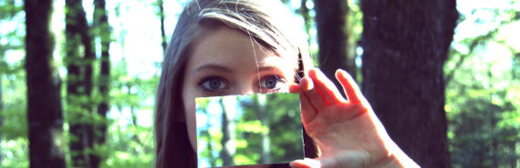woman holds a mirror under her eyes