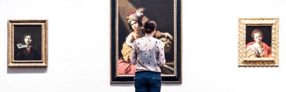woman looks art in museum