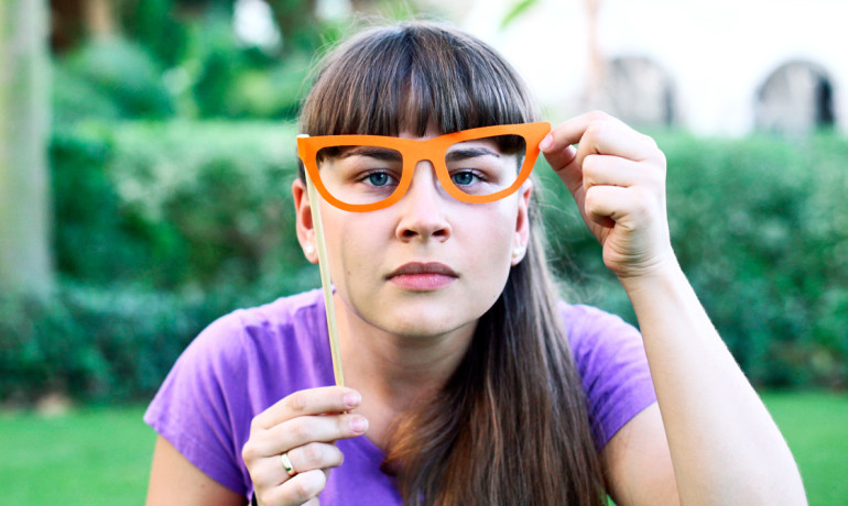 woman holds up paper glasses
