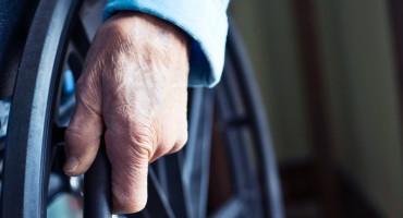 elderly person's hand on wheelchair