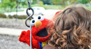 girl holds elmo doll on swing