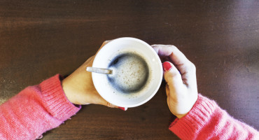 woman's hands hold a cup of coffee