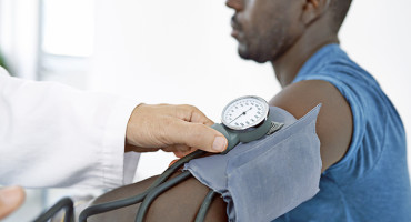 doctor checks a man's blood pressure