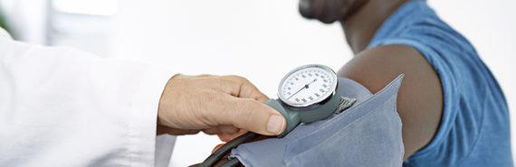 doctor checks a man's blood pressure