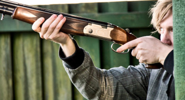 man aims shotgun