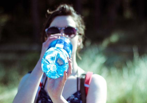 woman drinks from a blue bottle