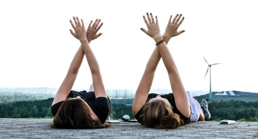 two women with arms in x's