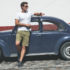 man standing beside a VW bug