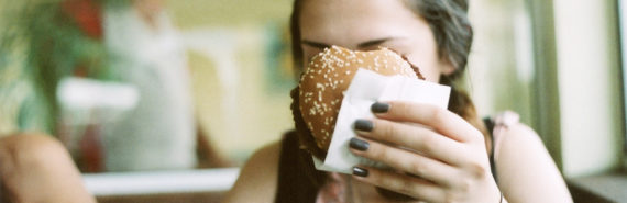 woman holds a burger