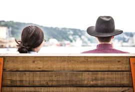 two heads, one hat above bench