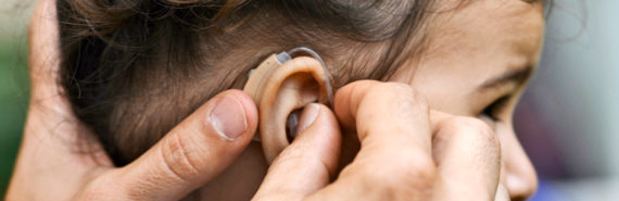 girl gets hearing aid put on