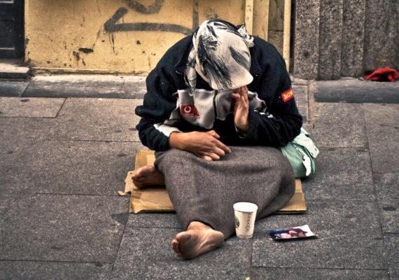 homeless woman sits on street