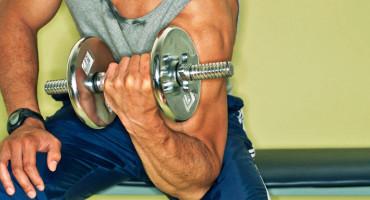 man sweats while lifting weights