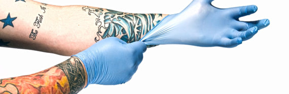 Man with tattooed arms pulls on surgical gloves.